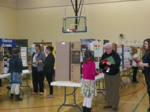 NCSD employee Gayle Schnorenberg visits with a participant! The success of the Science Fair each year is assisted by many community volunteers and NCSD staff and teachers.