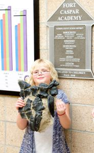"4th grade student at Ft. Caspar Academy, Kaitlin Trost, holds her cast of the foot of ""Dopota the Dinosour!"""
