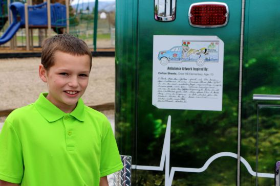 Crest Hill Elementary student, Colten Sheets, stands next to his winning entry which is proudly displayed on the side of the WMC Ambulance.